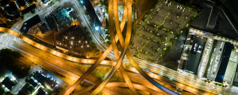 Vogelperspektive auf eine Straßenkreuzung bei Nacht